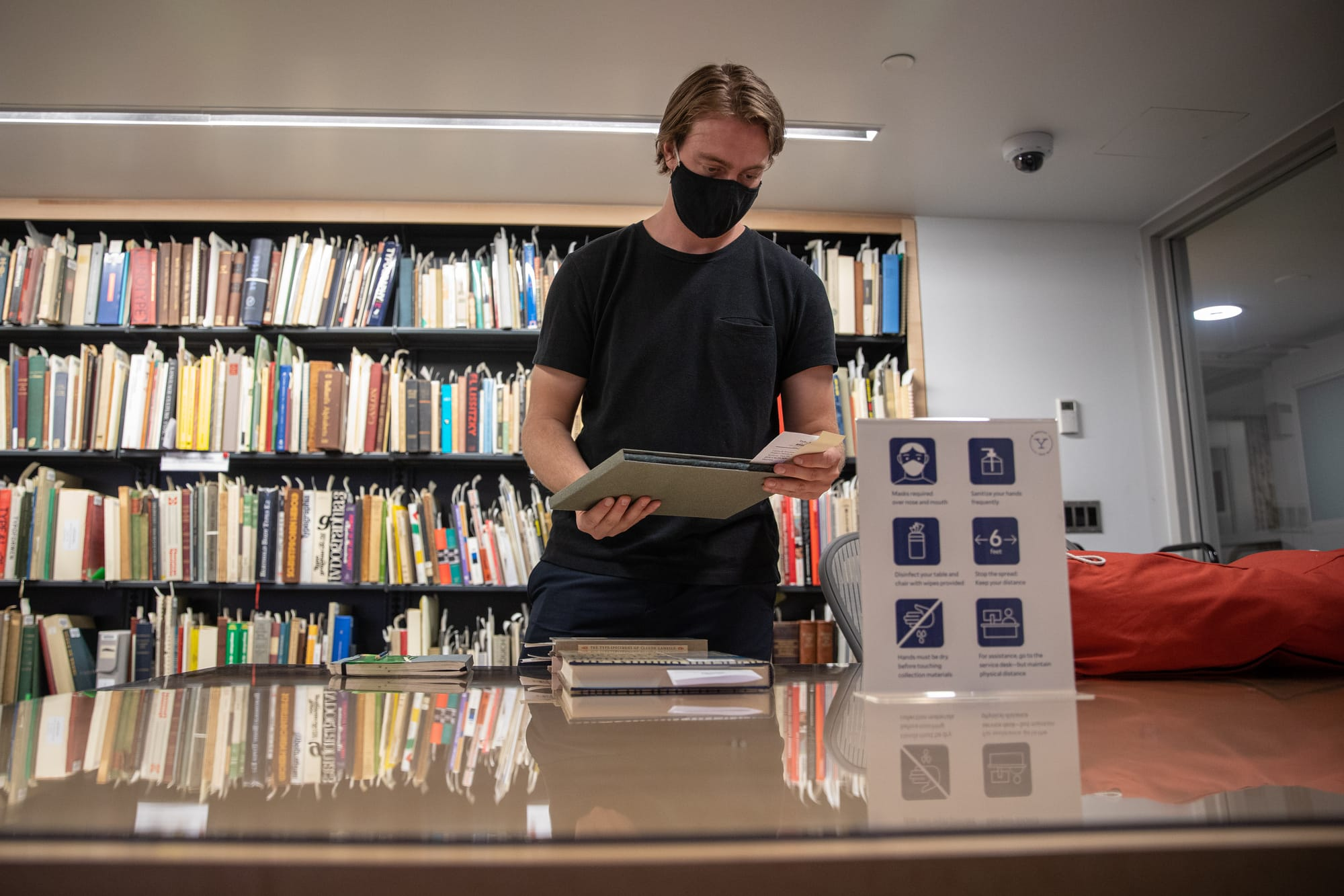 A masked student stands in front of book shelves and behind a table stacked with library books.