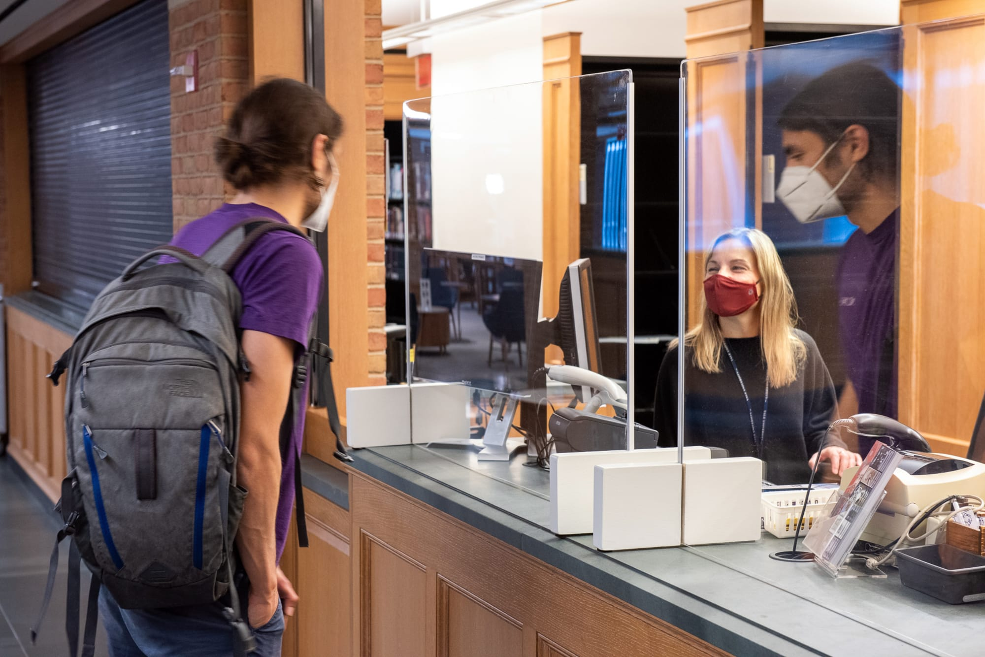 Library staff behind Plexiglass barrier assists student at service desk in Bass Library.