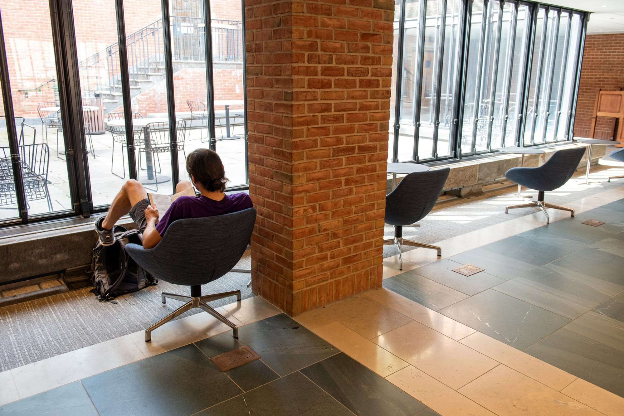 Male student with back to camera sitting in chair facing Bass LIbrary courtyard.