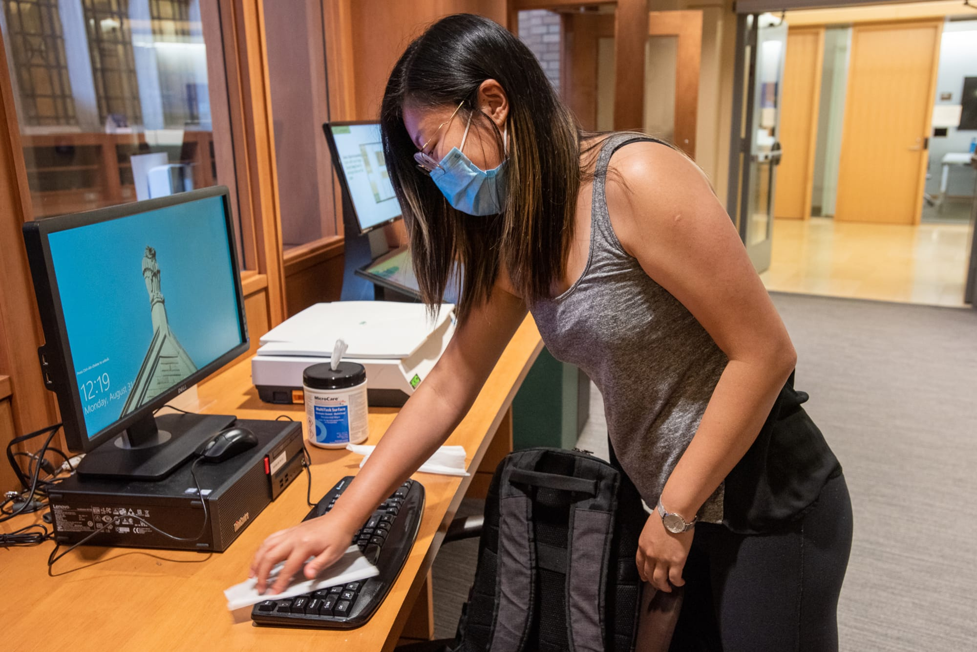Woman cleans computer keyboard with wipes in Bass Library.