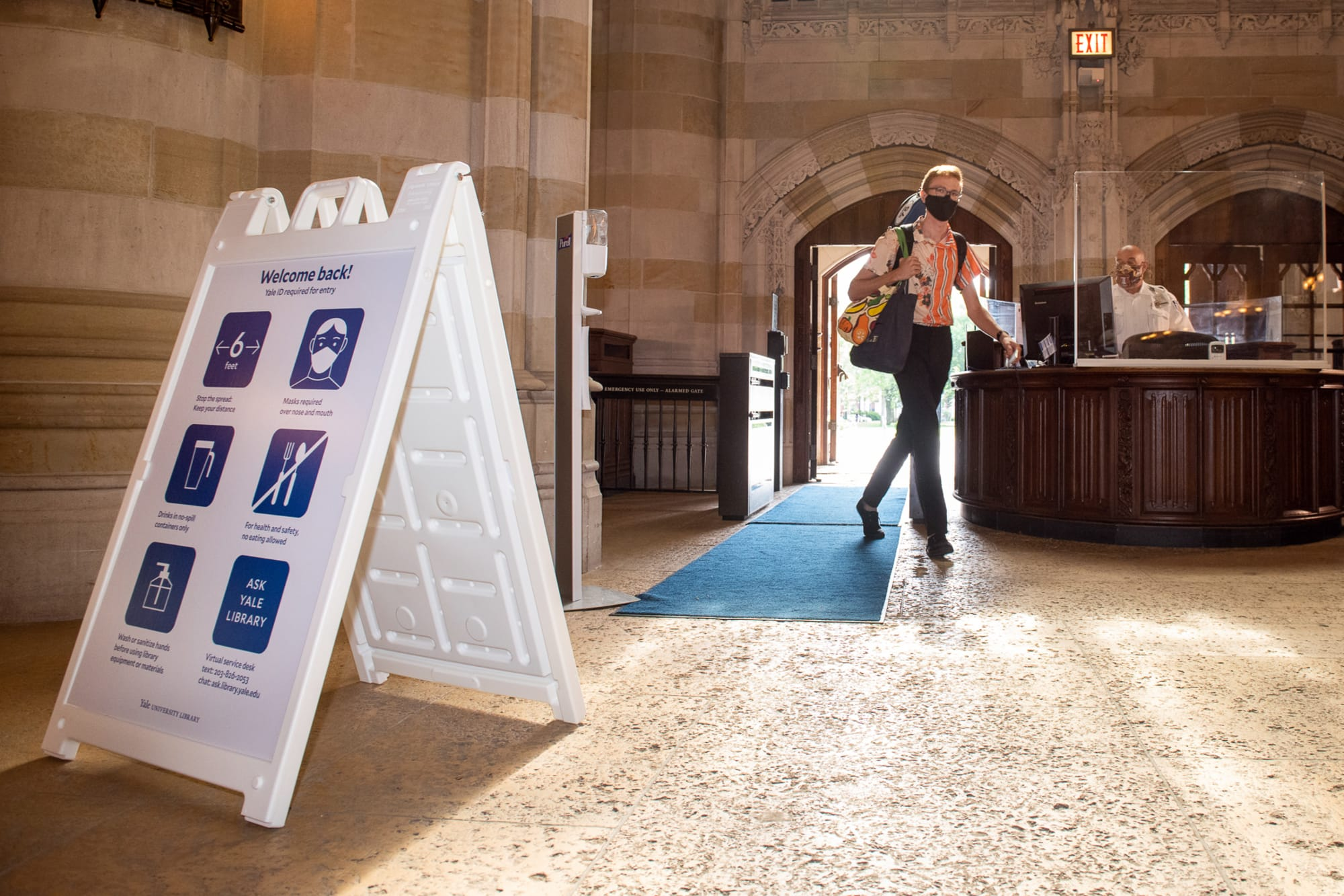 Man entering Sterling nave walking past library security officer at the entrance desk.