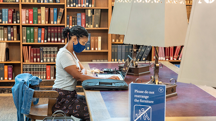 Student in mask with lap top sitting at reading room table
