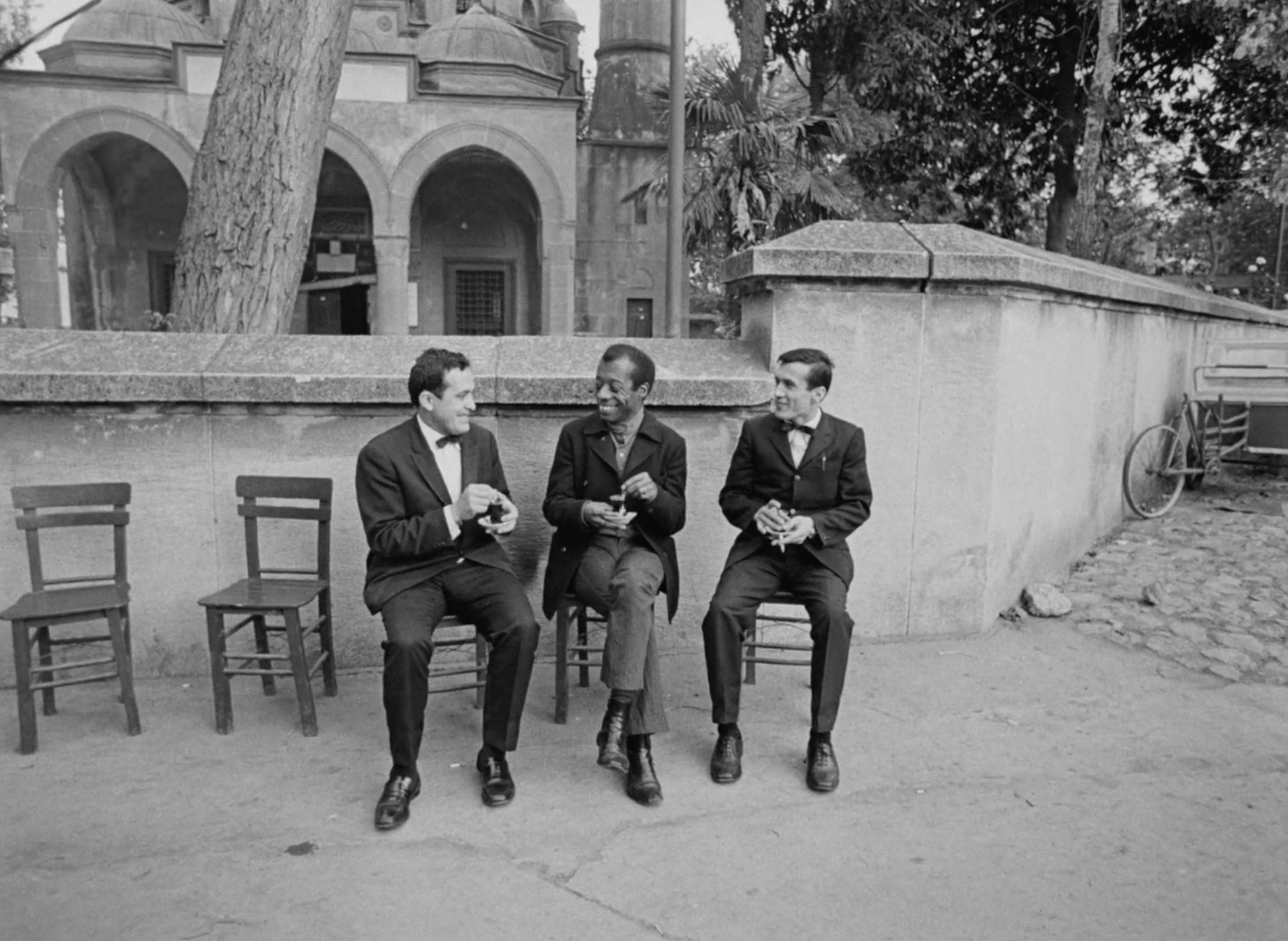 Three men sitting in front of building with arched doorways and domes