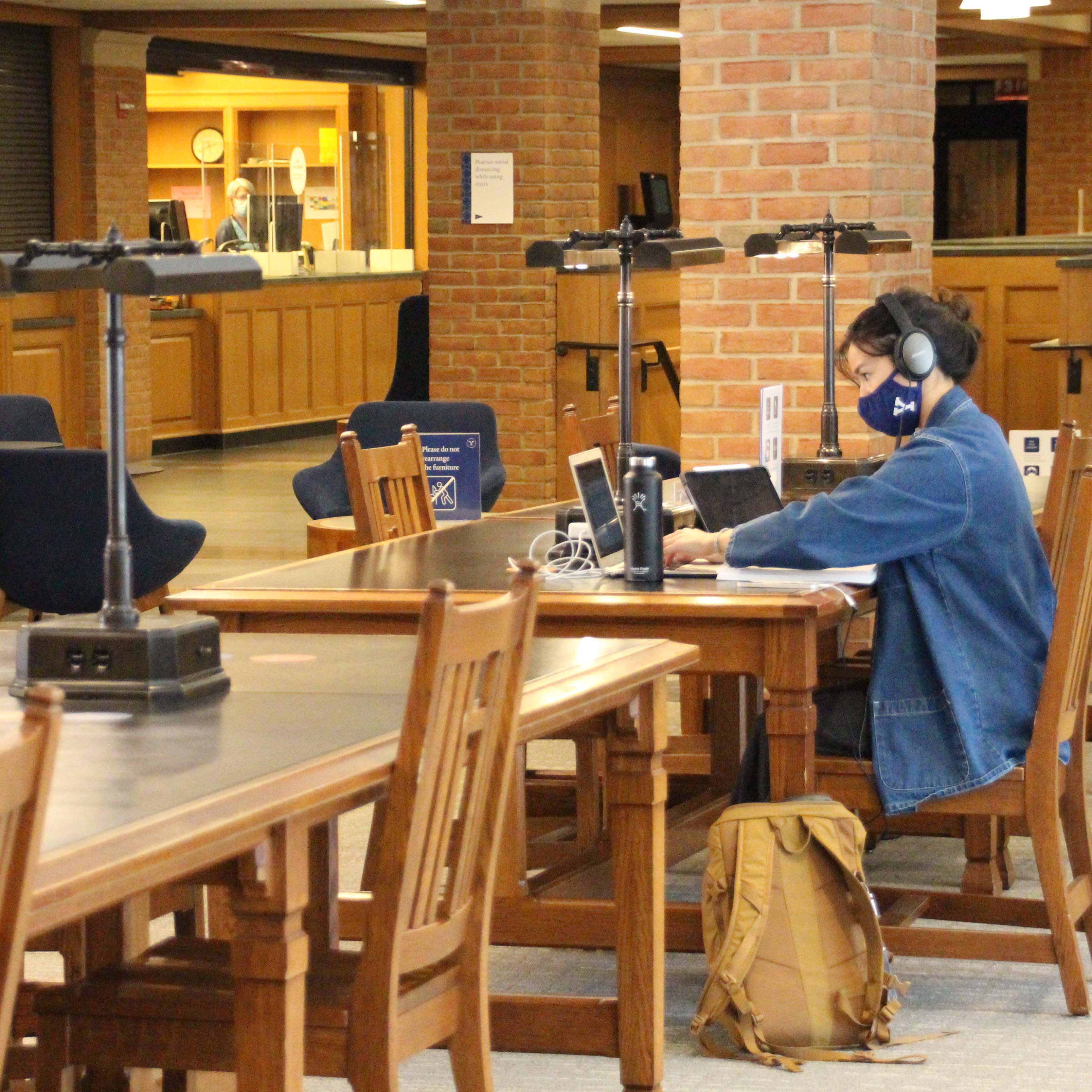A masked student working on a lap top in Bass Library