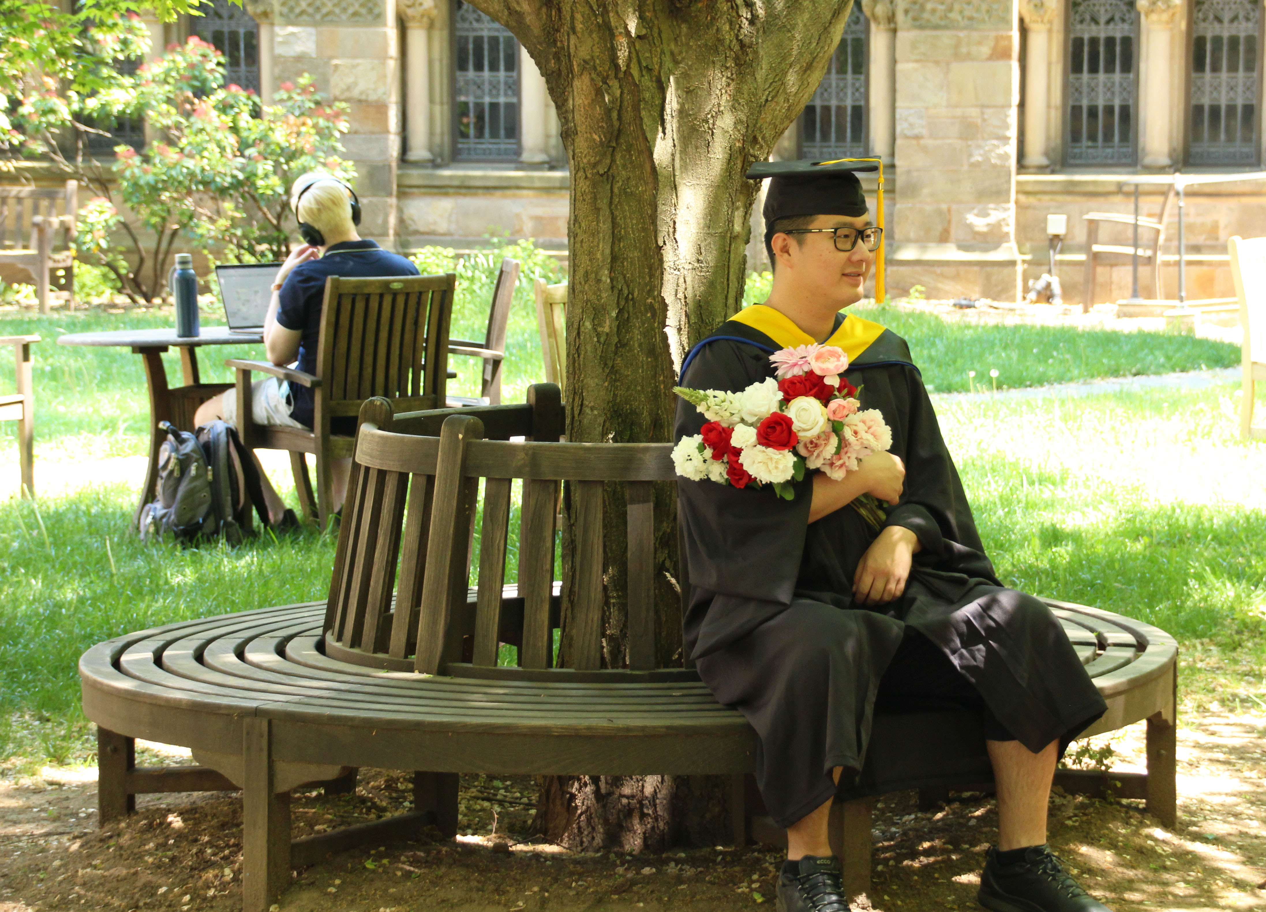 student sitting in courtyard with bunch of flowers