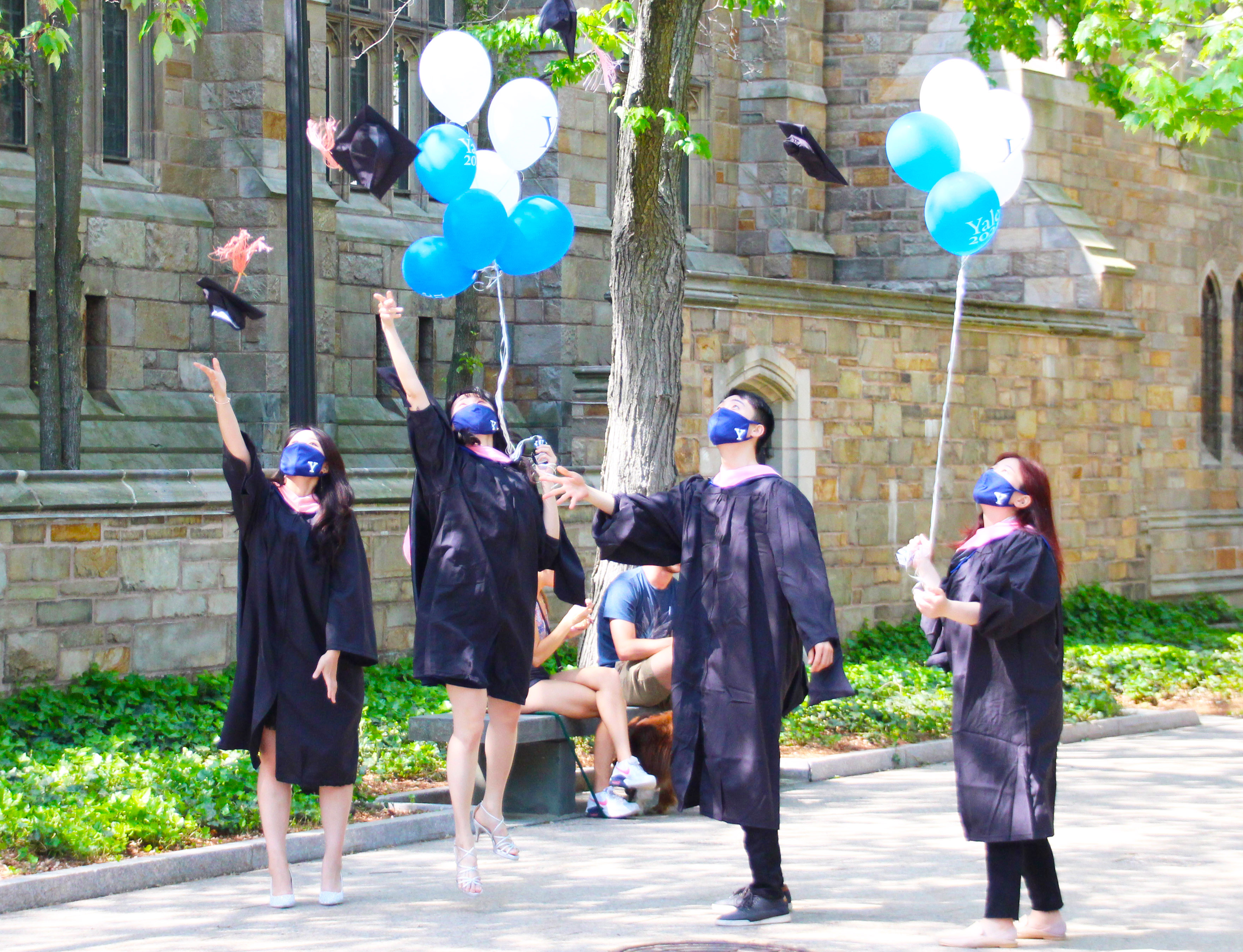 students  with balloons throwing mortar boards in air in front of library building