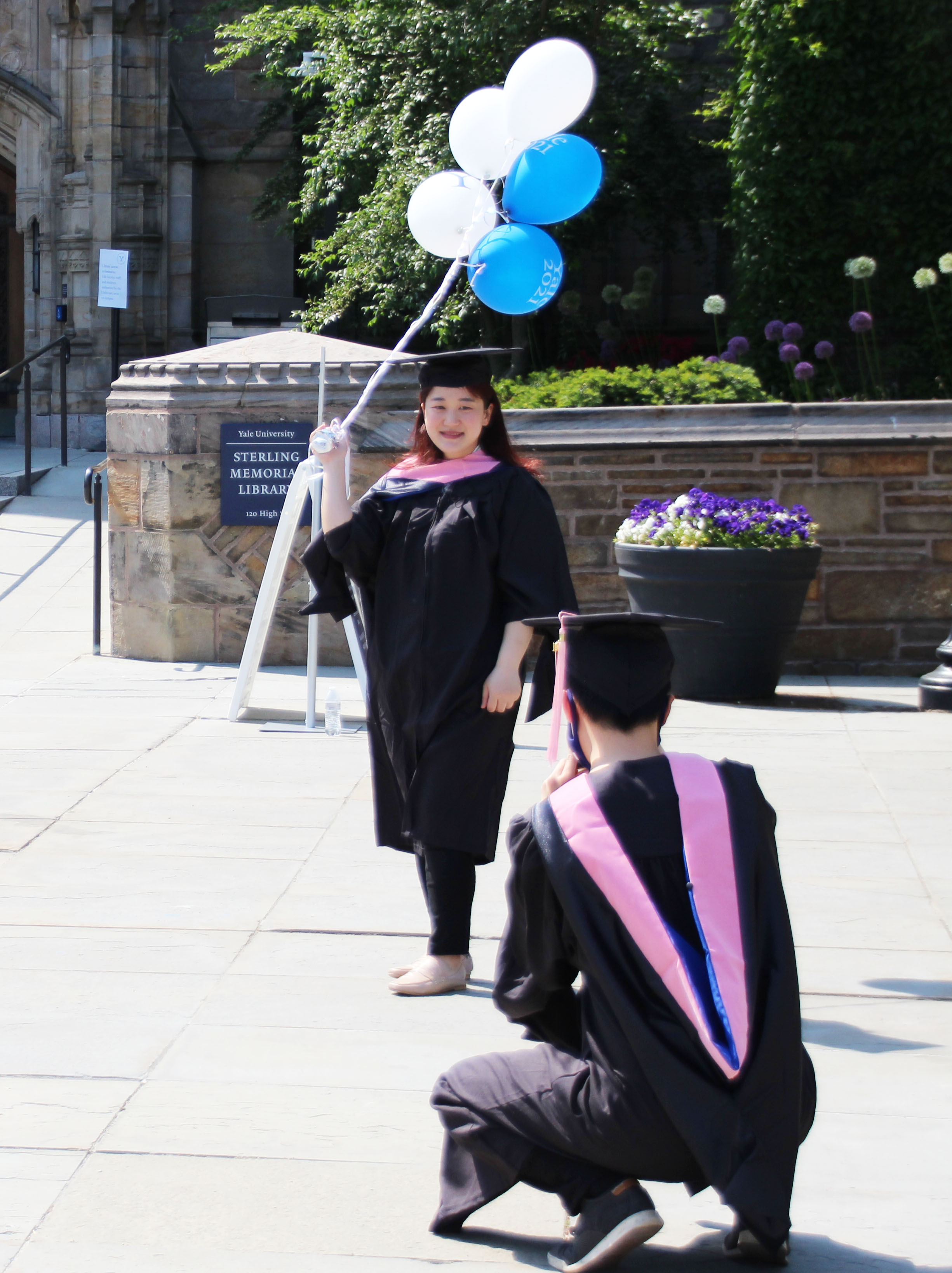 one student taking a photo of another with balloons