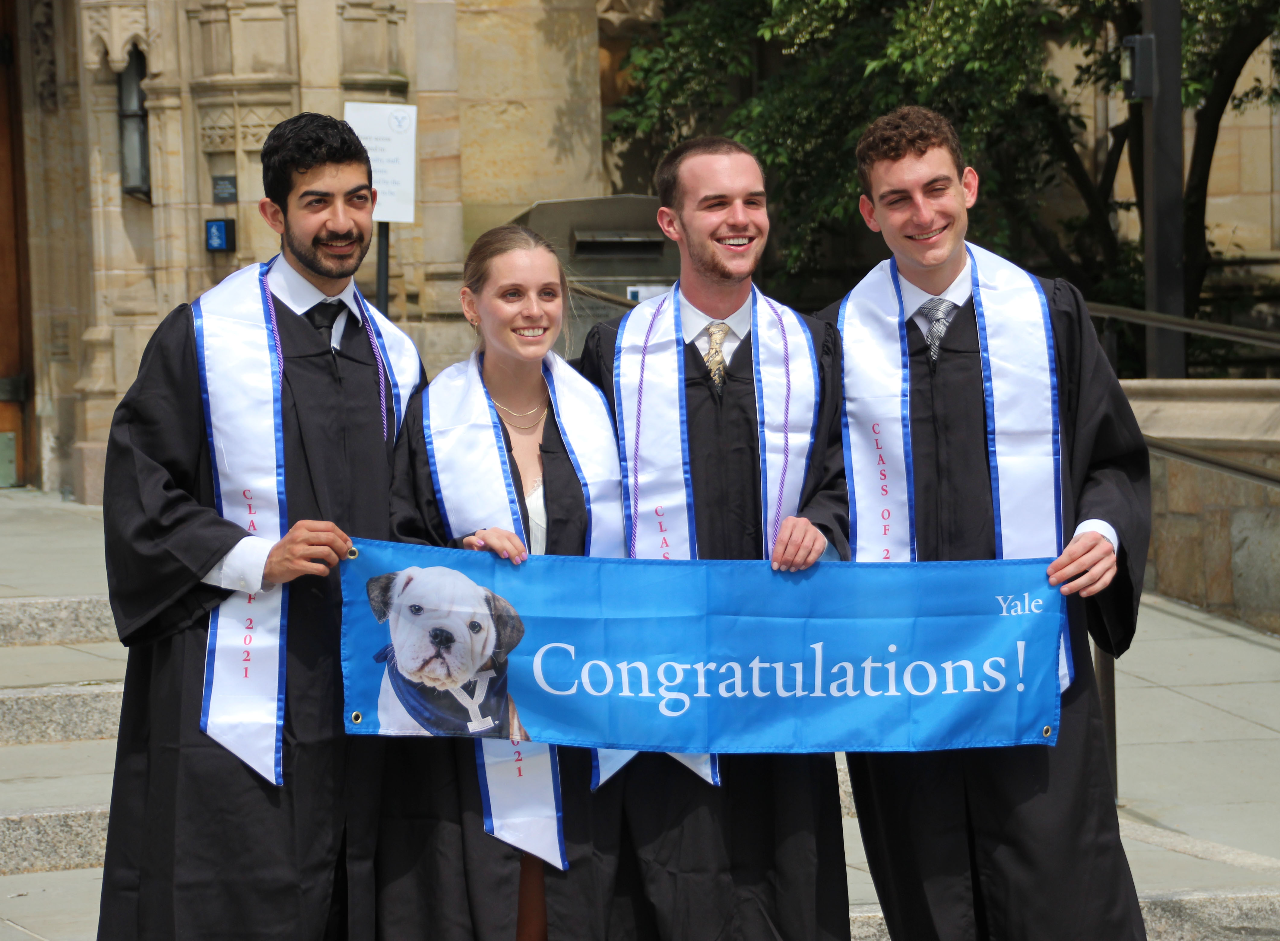 Four students in front of library with congratulatiions banner