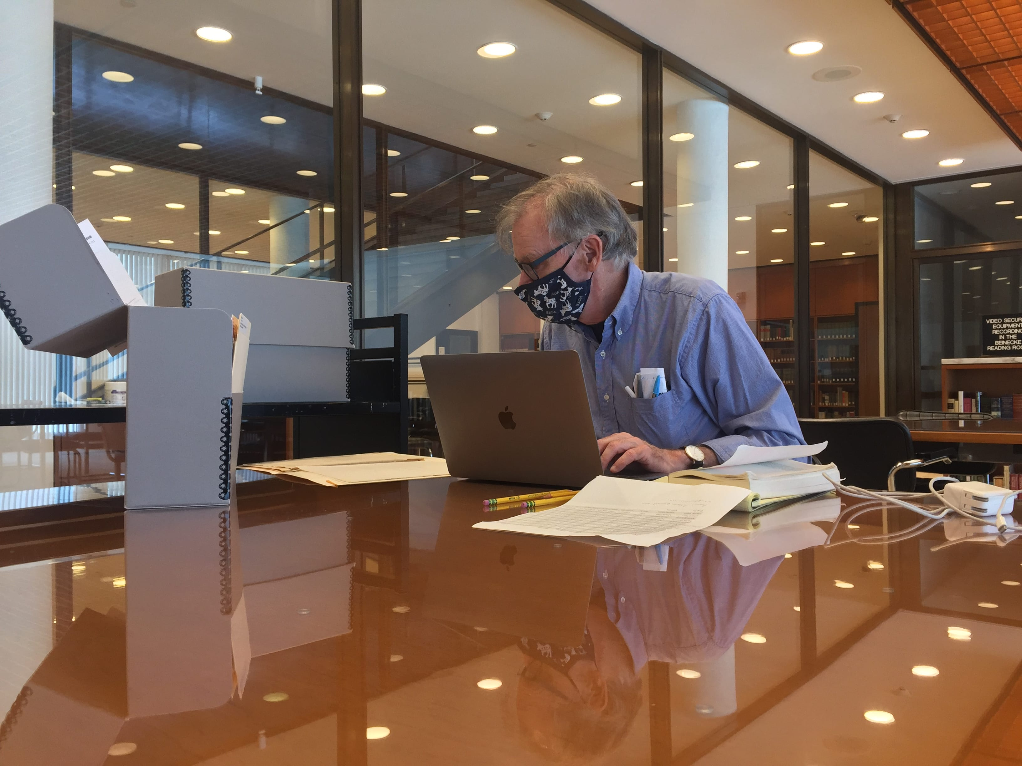 Masked Yale professor in the reading room with lap top and papers