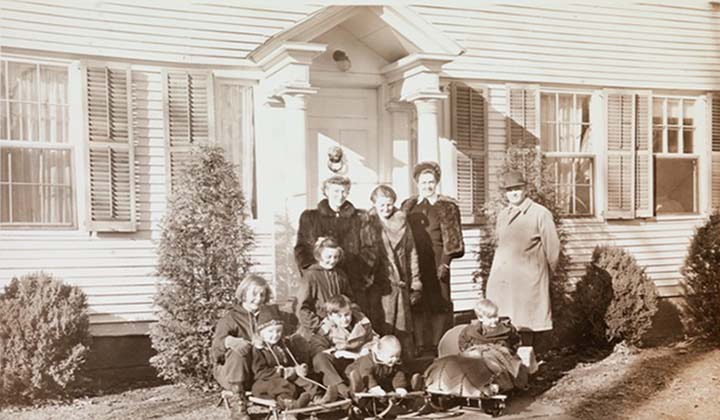 Black and white group photo of three women and a man standing in front of the front door of a clapboard house, a group of children in front, all wearing winter coats, ca. 1941