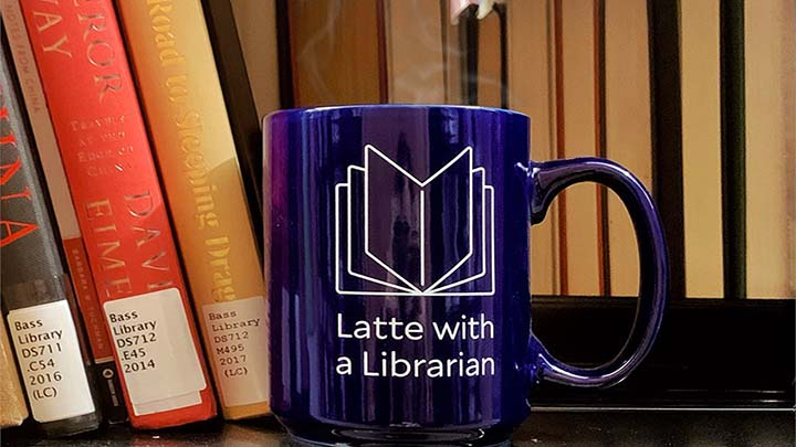 blue mug in a bookshelf, with Latte with a Librarian engraved on it