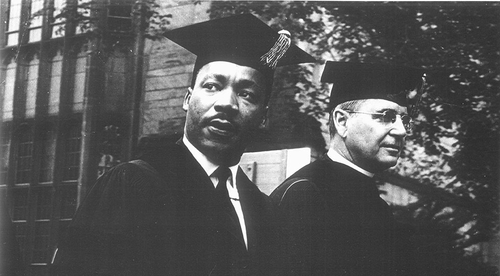 A black and white photo of Martin Luther King and President Kingman Brewster wearing cap and gown