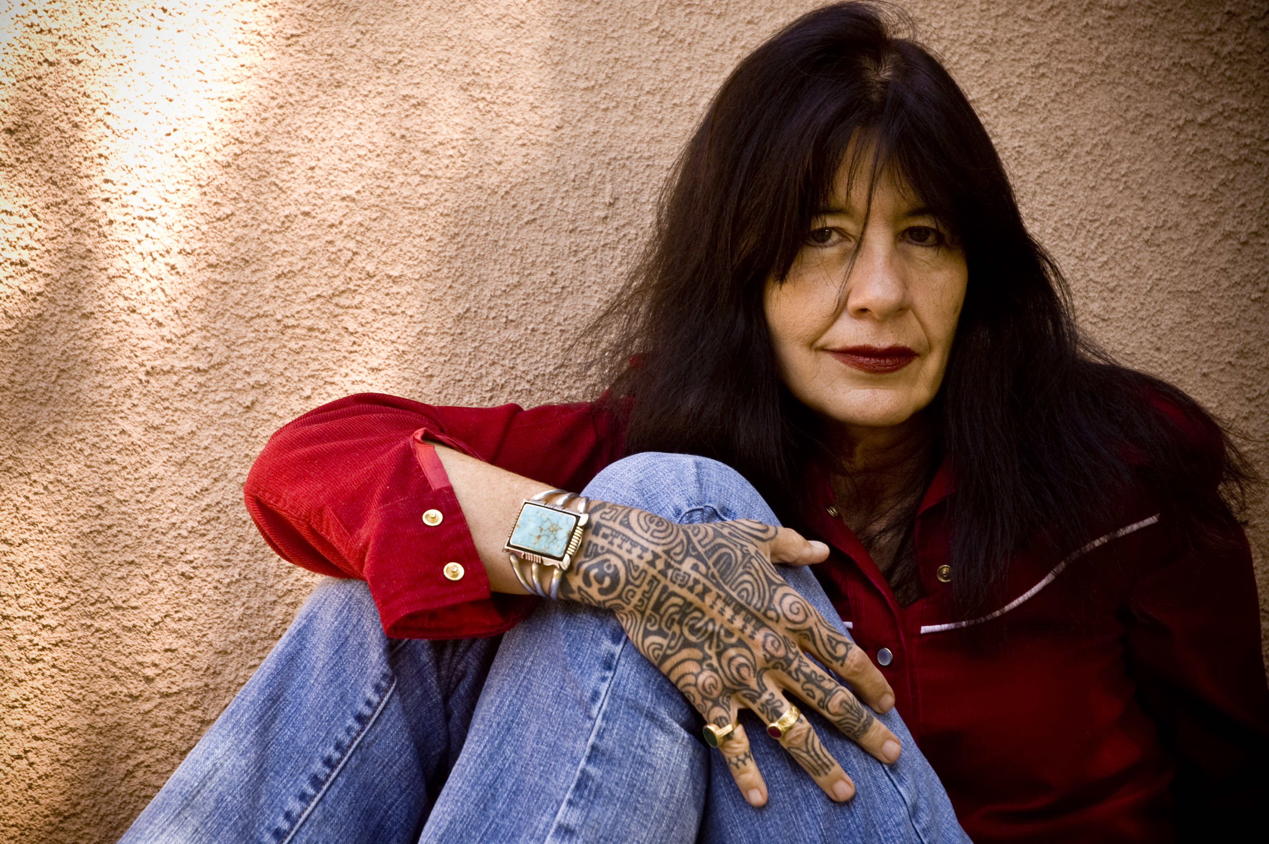 An image of a seated woman leaning on the wall showing a hand with tattoo