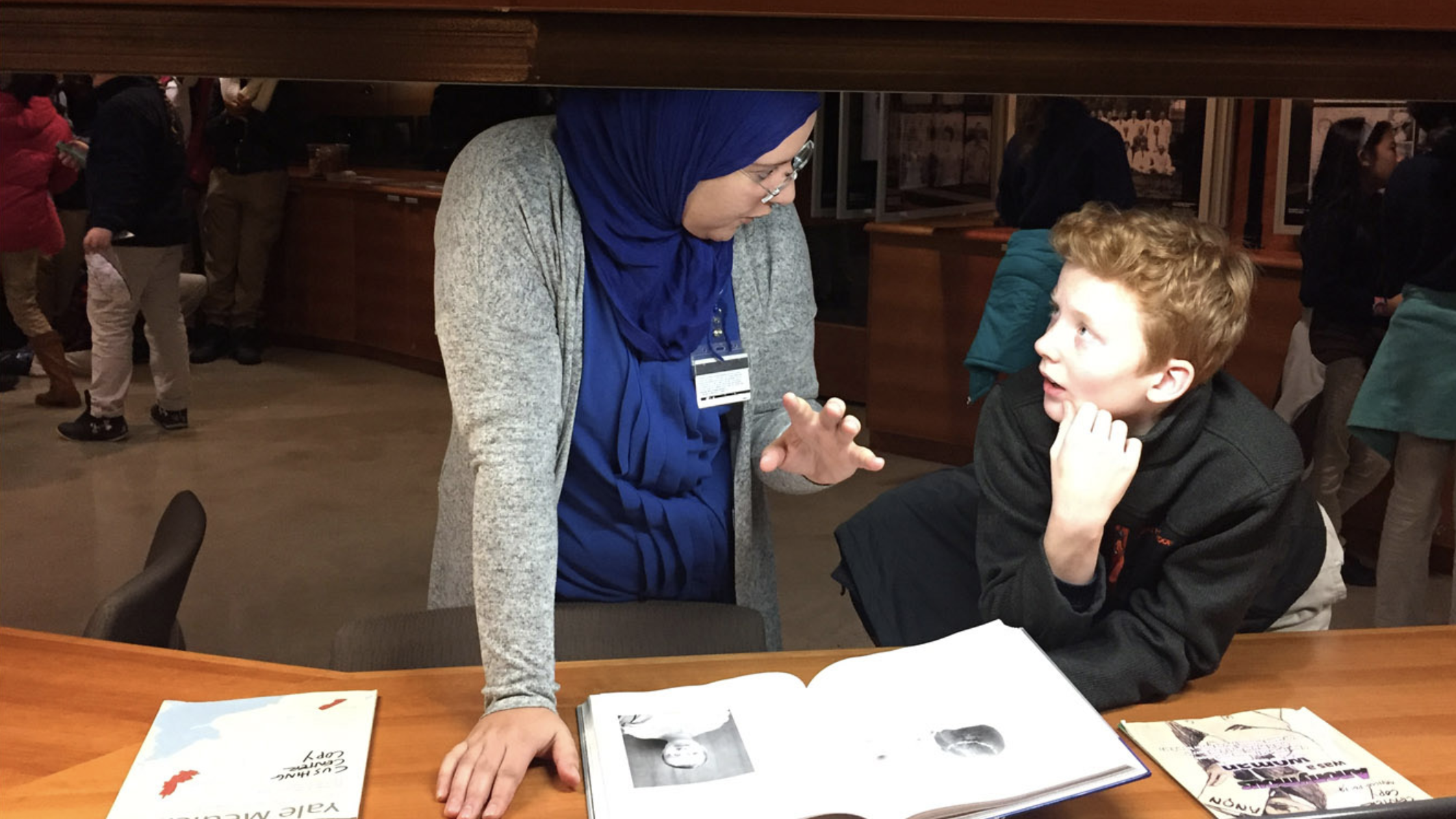 A woman in blue jihad talking to a boy and an open book in front of them