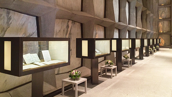 Row of display cases in Beinecke Library holding printed collection materials