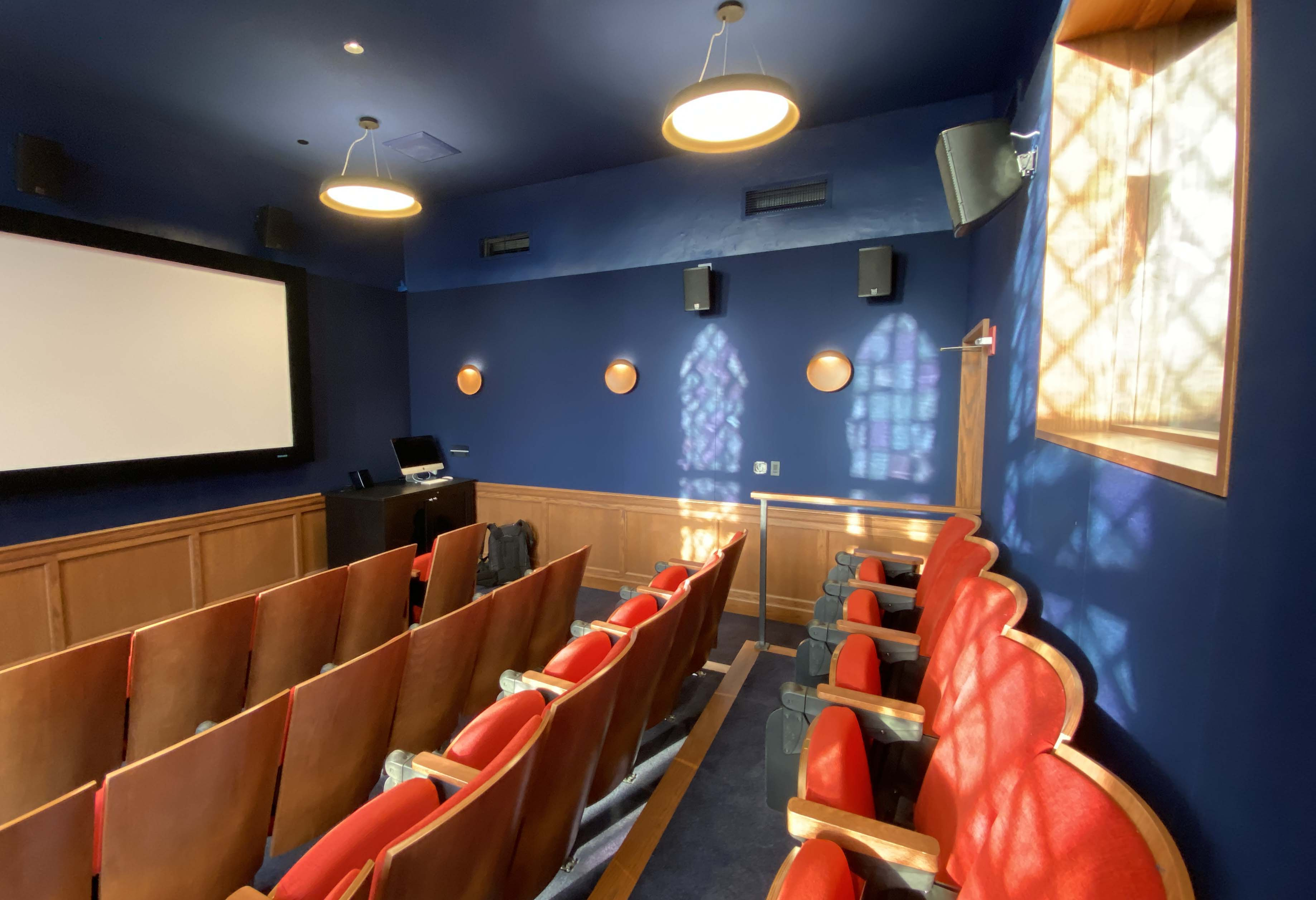 Room with large white screen and rows of red seats