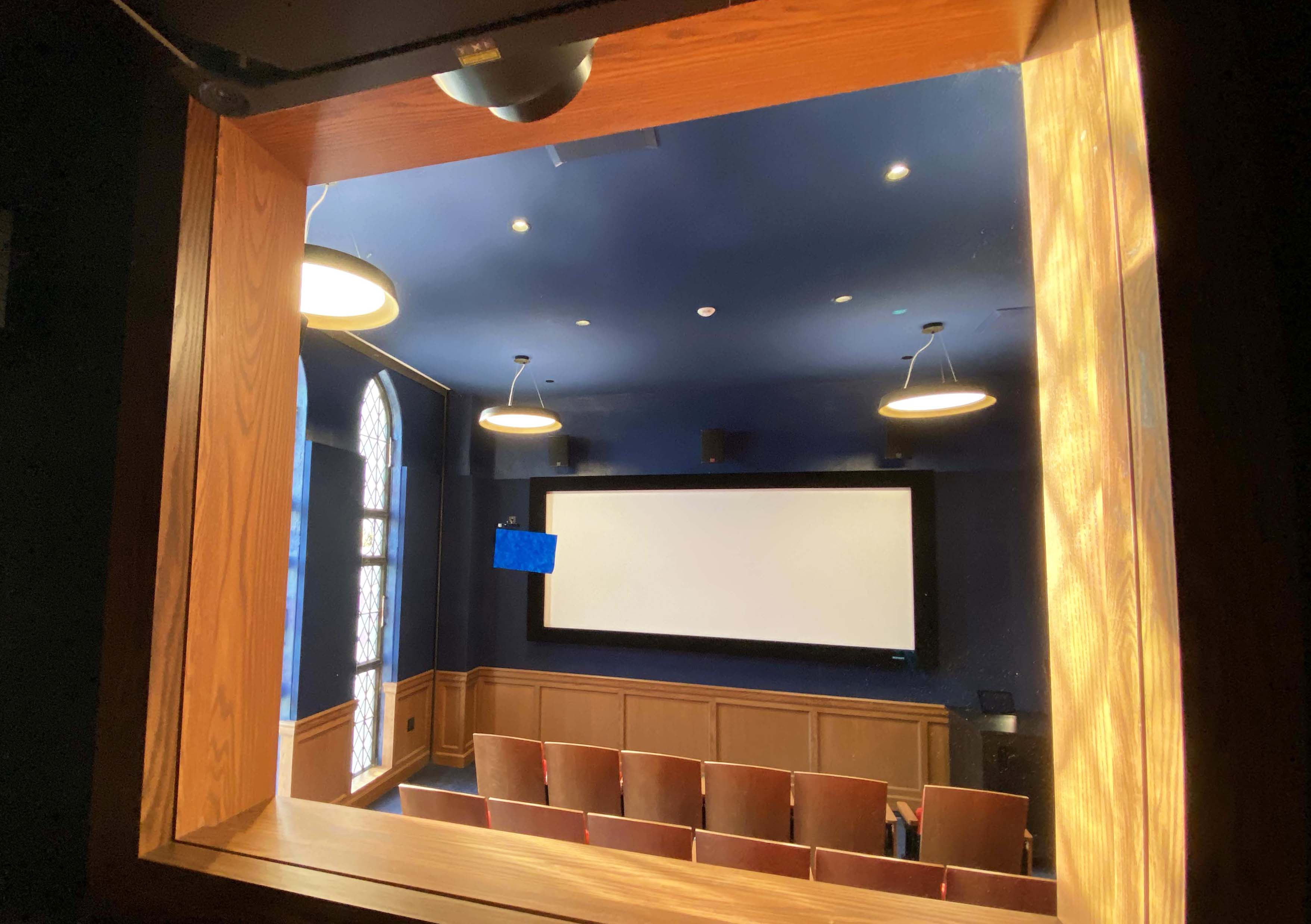 View through window of large screen viewed from projection room to the screening room