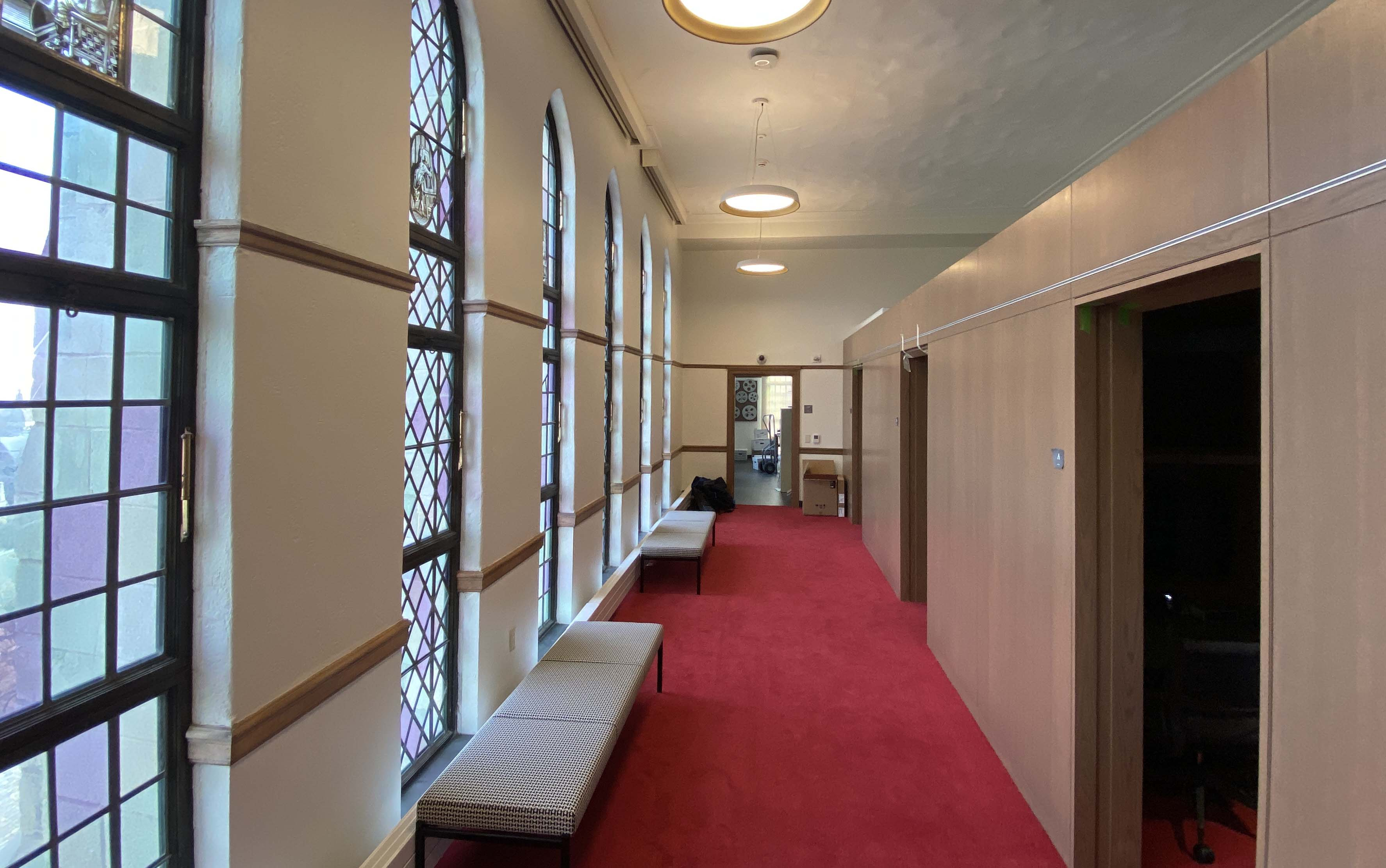 Long corridor with stained glass windows to left and individual viewing booths to the right