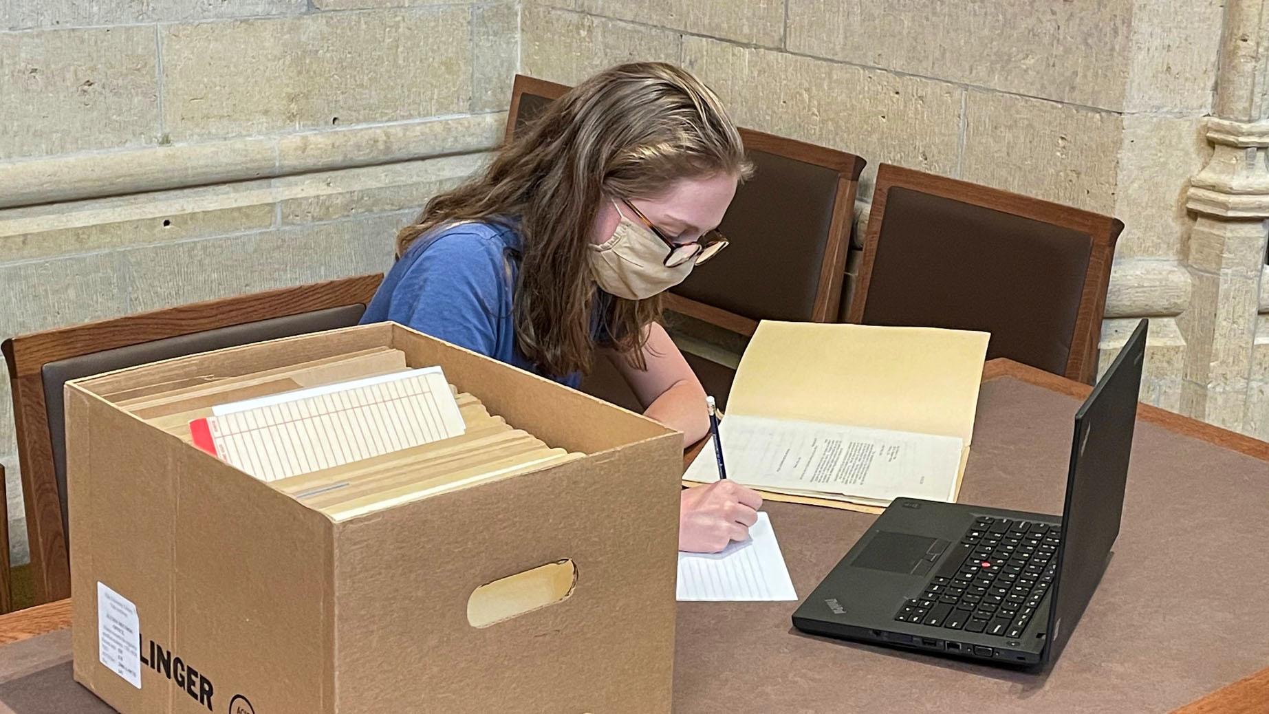 Woman writes at a desk beside a box of manuscripts
