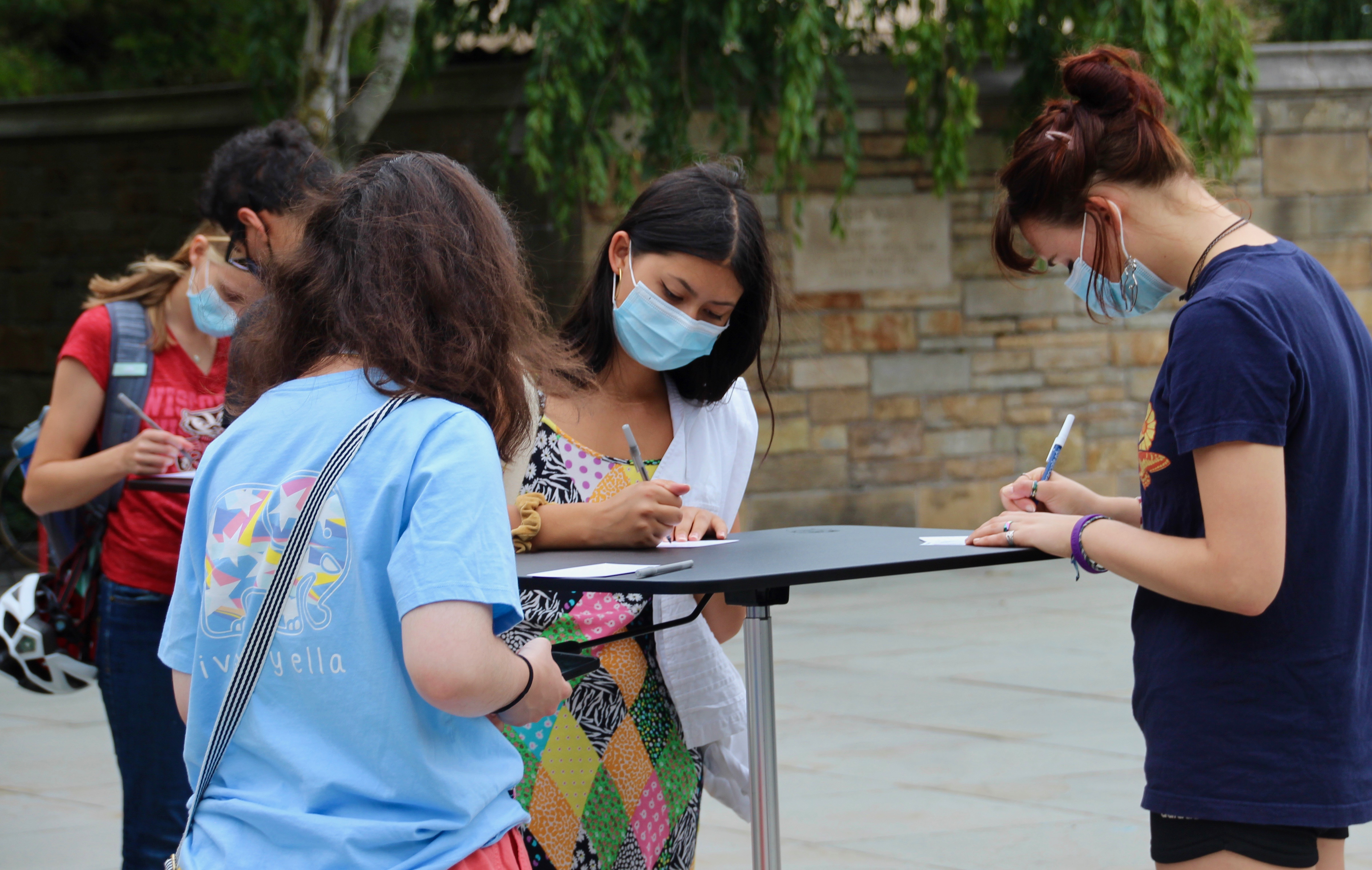 Four female students writing postcards at table