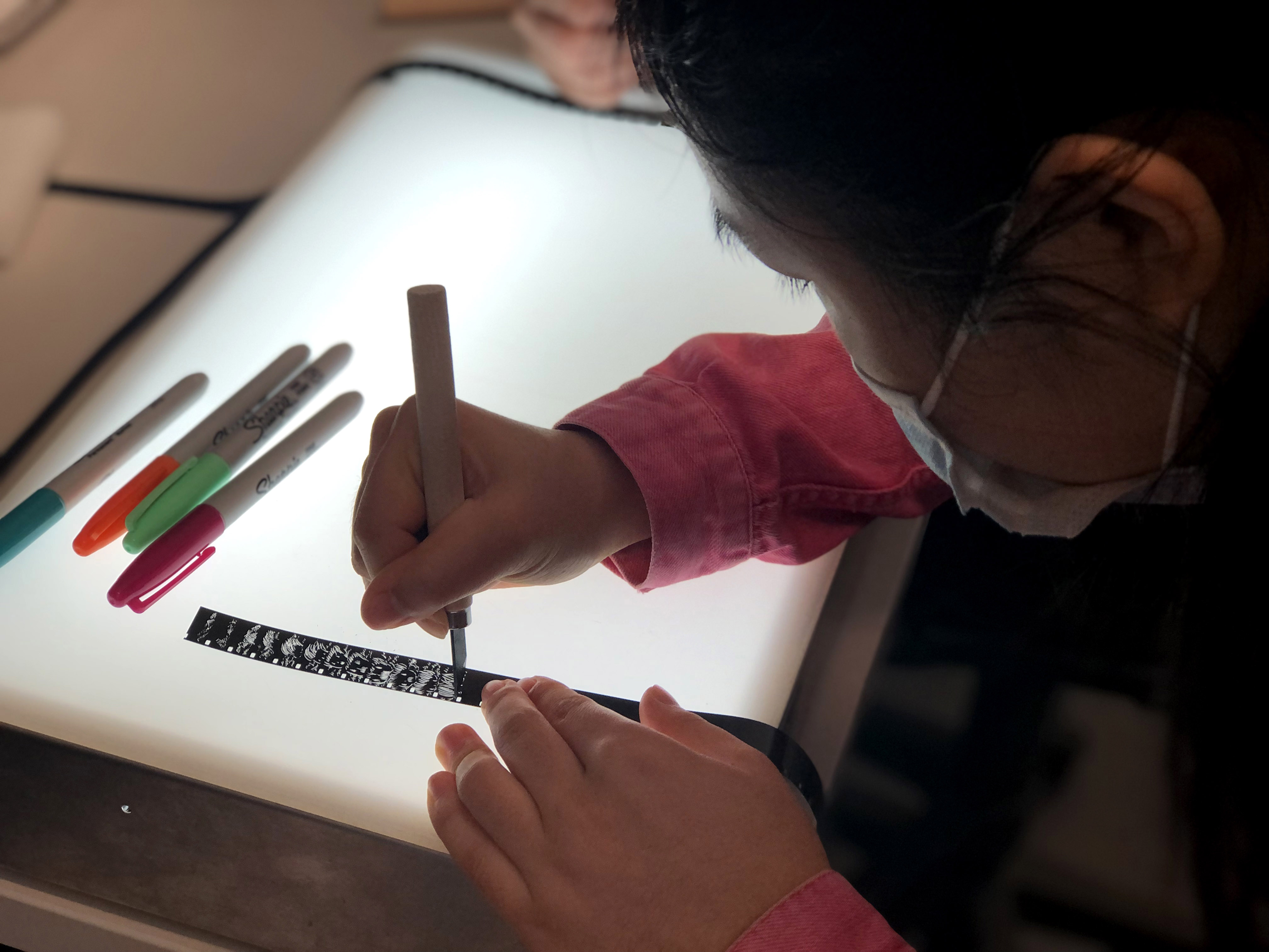 Female student draws on film strip on lightbox