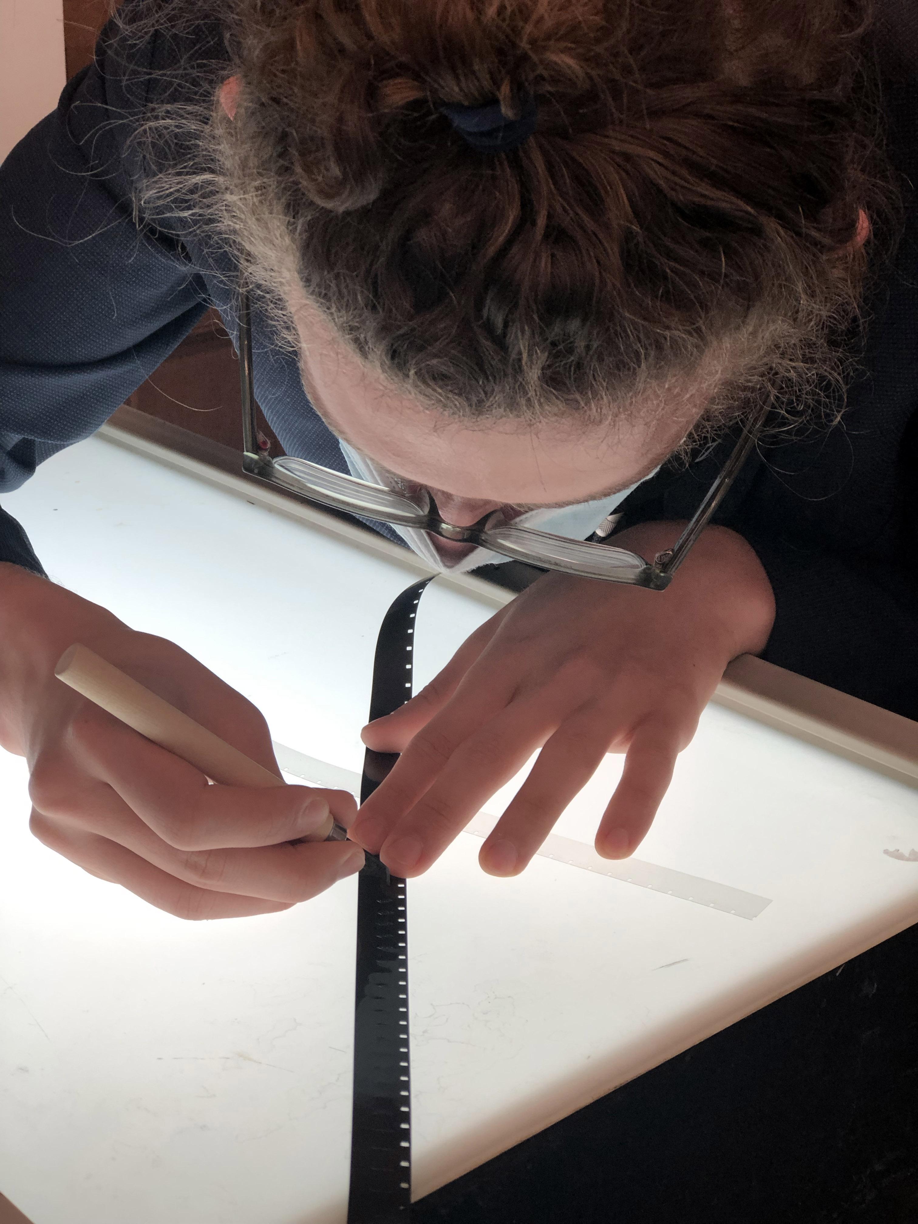 Female student drawing on film strip on lightbox