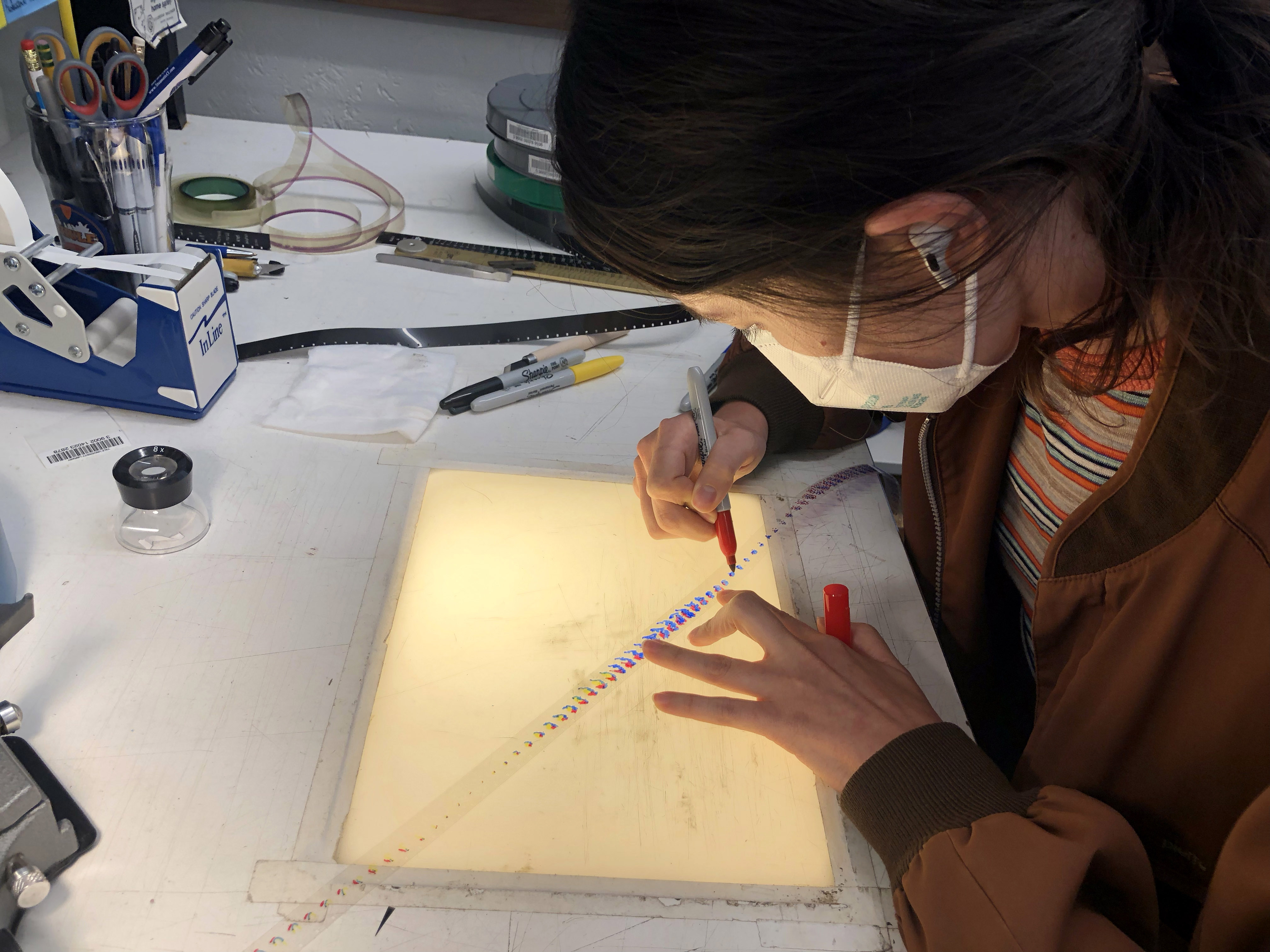 Female student draws in color on a film strip