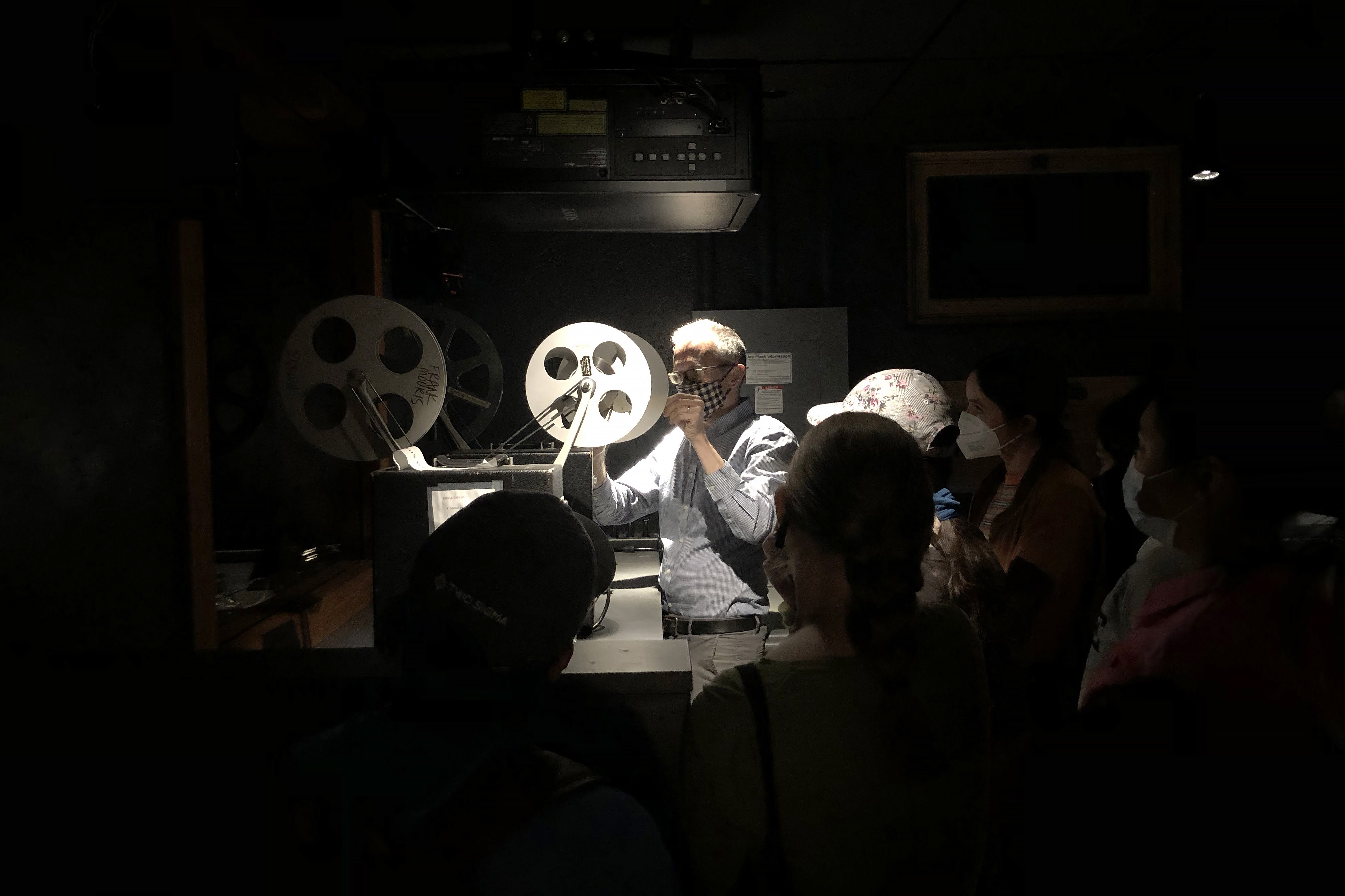 Man showing students how to use a film projector