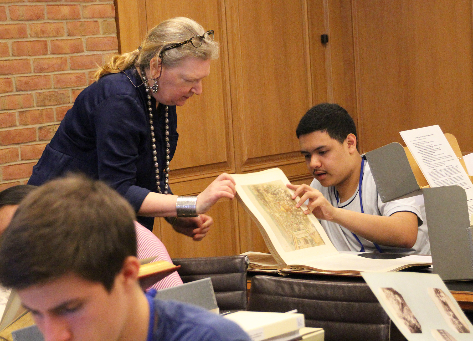 Librarian showing a collection item to a student
