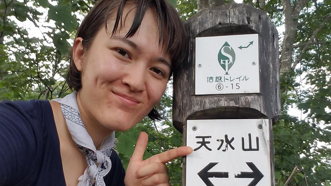 Photo of Yale student Sarah Adams pointing to a sign post on the Shinetsu Trail in Japan
