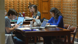 Students with laptops studying at library tables, background of card catalogs