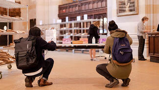 Two students writing postcards while kneeling at a desk in the Sterling nave