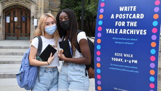 Two female students with library-branded journals standing next to the event posters