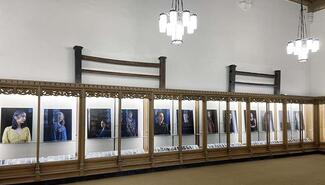 series of portraits lined up in a glass display