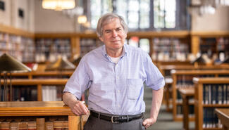 Fred Shapiro standing in the library, surrounded by shelves of books