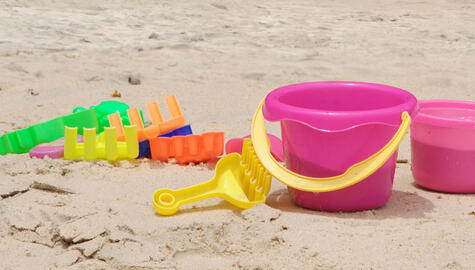 Photo of plastic spades and a bucket in a sand box.