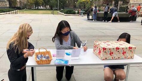 Three students writing postcarsd at a table